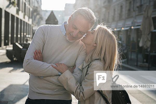 Frau flüstert einem älteren Mann auf der Straße ins Ohr