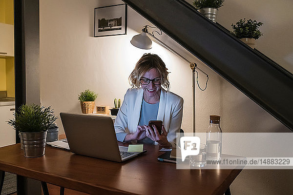 Woman working at laptop and texting in home office
