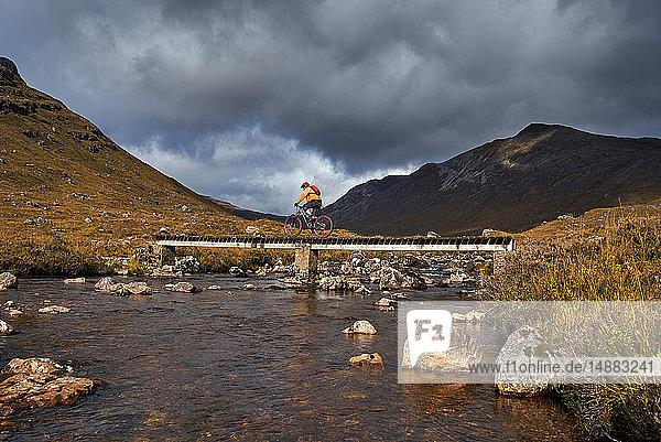 Männlicher Mountainbiker radelt über Steg in Bergtal-Landschaft  Achnasheen  Schottische Highlands  Schottland