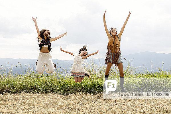Freunde und Mädchen springen in die Luft  Città della Pieve  Umbrien  Italien