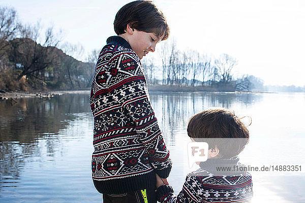 Junge und kleiner Bruder im passenden Pullover halten Händchen am Seeufer  Comer See  Lecco  Lombardei  Italien