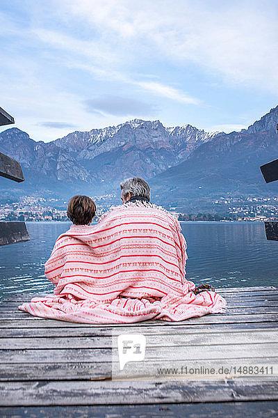Junge und Vater in eine Decke gewickelt auf dem Seepier  Rückansicht  Comer See  Onno  Lombardei  Italien