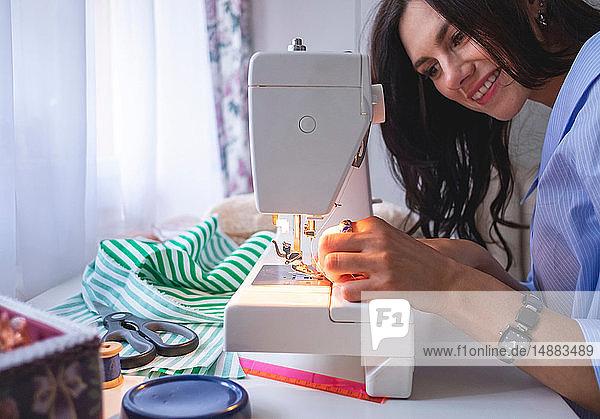 Woman threading sewing machine needle beside window