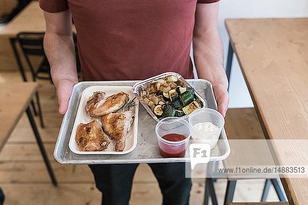 Kunde mit Tablett mit gegrilltem Hähnchen  Gemüse und Dip-Sauce im Restaurant