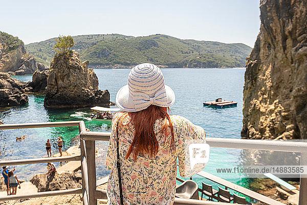 Tourist relaxing by La Grotta Beach with rock formations in Paleokastritsa  Corfu  Kerkira  Greece