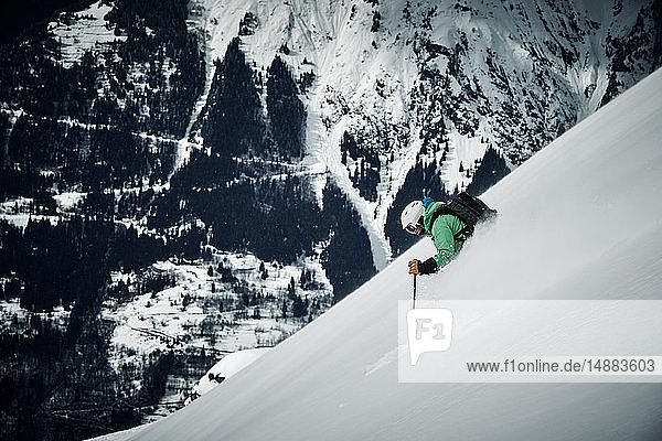 Männlicher Skifahrer  der einen steilen Berghang hinunterfährt  Alpe-d'Huez  Rhône-Alpes  Frankreich