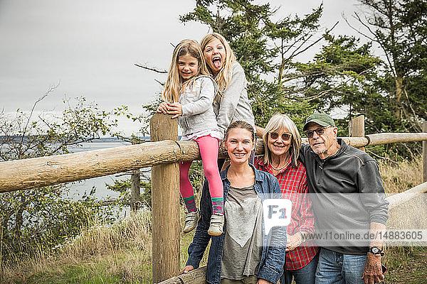 Mädchen sitzen mit Mutter und Großeltern auf dem Zaun  Port Townsend  Washington  Kalifornien  USA