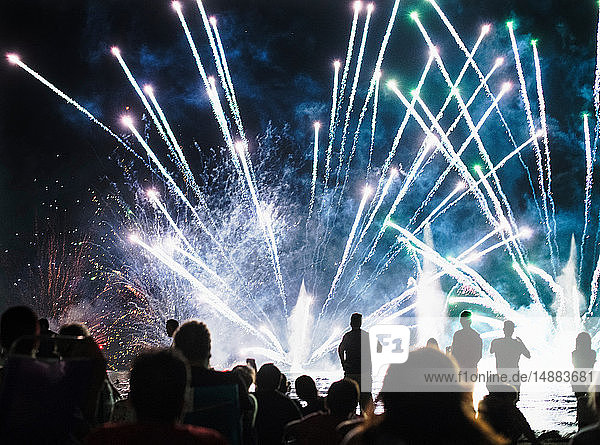 Group of people watching fireworks display at night