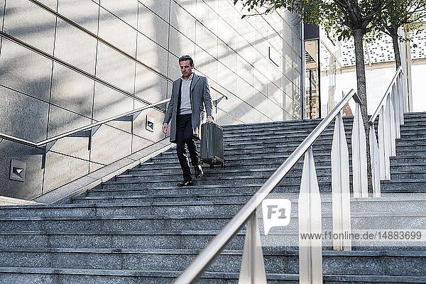 Geschäftsmann geht mit Rollgepäck die Treppe hinunter