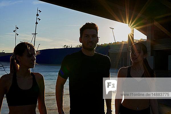 Freunde im Sportstadion bei Sonnenuntergang
