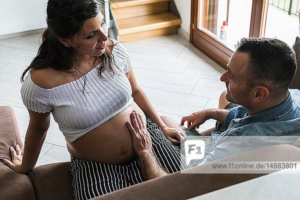 Pregnant couple feeling belly on sofa