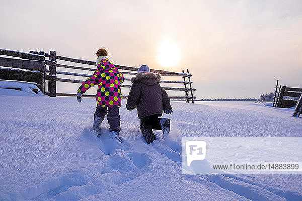 Boy and girl trudging through snow covered landscape  rear view