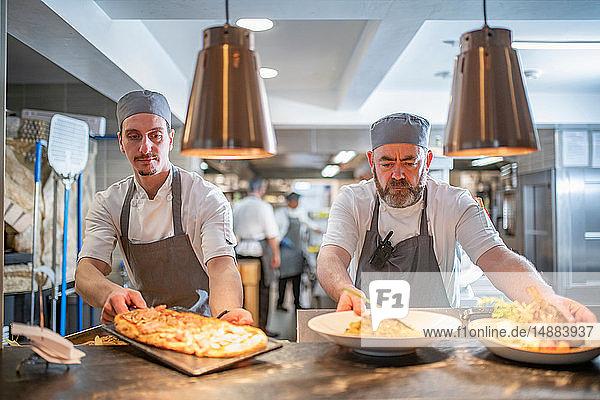 Köche präsentieren Gerichte in der italienischen Restaurantküche