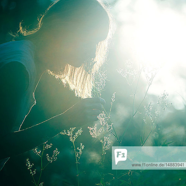 Frau riecht Blumen im Wald