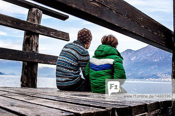 Junge und Vater sitzen am Pier am Seeufer  Rückansicht  Comer See  Onno  Lombardei  Italien