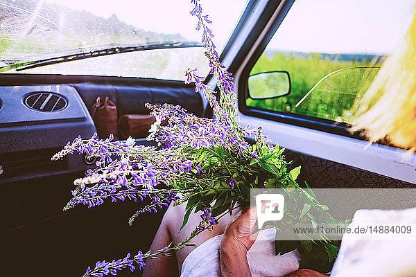 Frau sitzt im Auto mit violettem Wildblumenstrauss  Blick über die Schulter