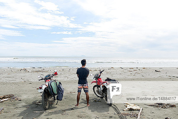Motorcyclist carrying surfboard on sandy beach  Abulug  Cagayan  Philippines