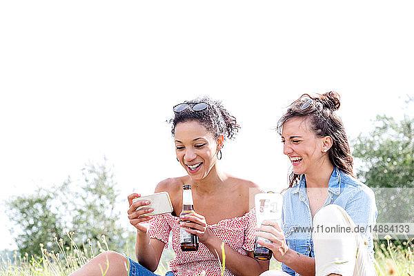 Freunde überprüfen Mobiltelefon im Freien