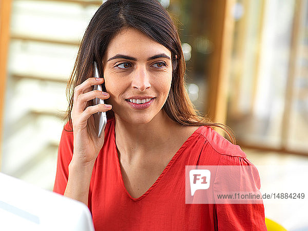 Frau  die am Computer arbeitet und im Büro ein Mobiltelefon benutzt