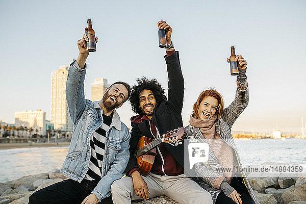 Porträt von drei glücklichen Freunden mit Gitarre  die bei Sonnenuntergang an der Küste Bierflaschen hochheben