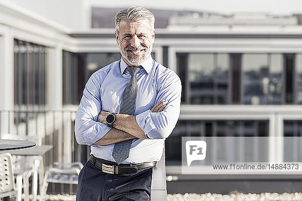 Porträt eines lächelnden  selbstbewussten  reifen Geschäftsmannes auf der Dachterrasse