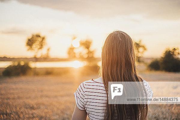 Rückenansicht einer jungen Frau beim Sonnenuntergang