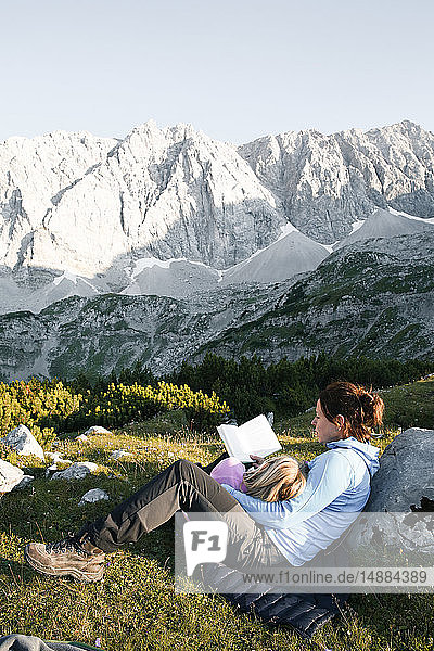 Austria  Tyrol  mother and daughter reading book in mountainscape
