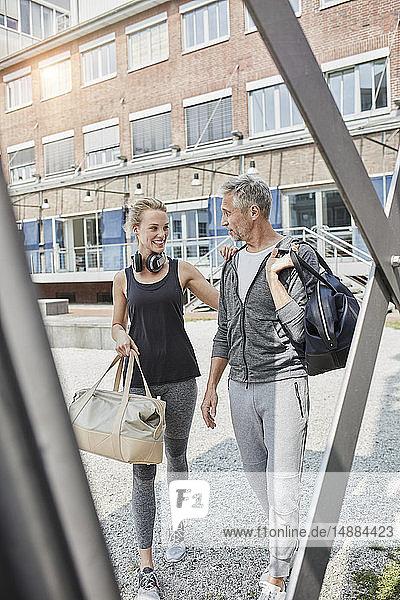 Junge Frau und reifer Mann mit Sporttasche auf dem Weg zum Fitnessstudio