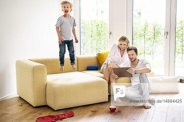 Glückliche Familie zieht in ihr neues Zuhause ein  Junge springt auf die Couch