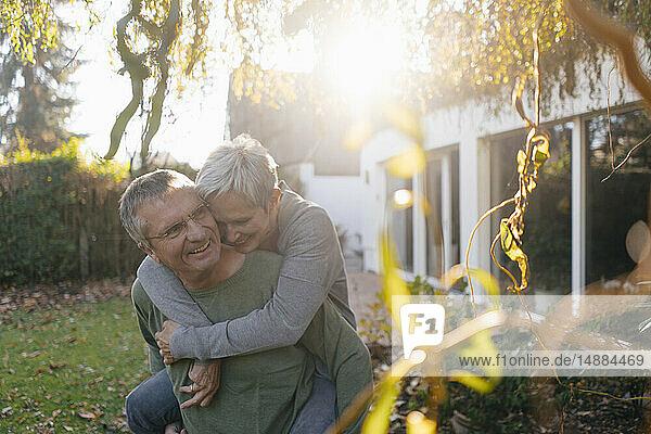 Glücklicher älterer Mann trägt Frau huckepack im Garten