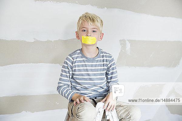 Porträt eines Jungen mit zugeklebtem Mund  der auf einer zu renovierenden Leiter auf dem Dachboden sitzt