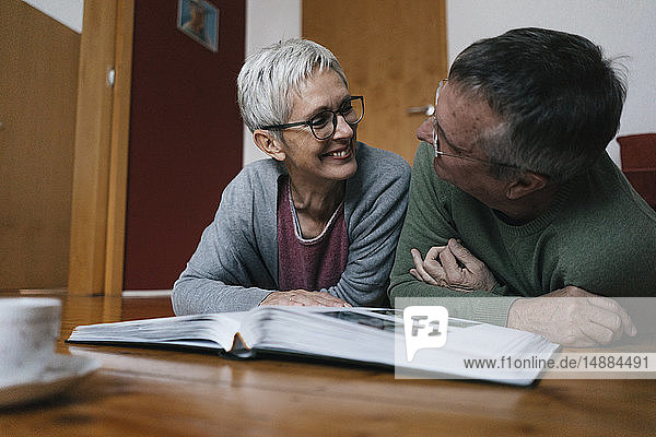 Glückliches älteres Ehepaar zu Hause auf dem Boden liegend mit Fotoalbum