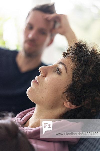 Mann beobachtet seine Frau beim Entspannen auf der Couch