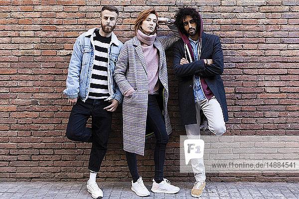 Porträt von drei ernsthaften Freunden  die an einer Ziegelmauer stehen