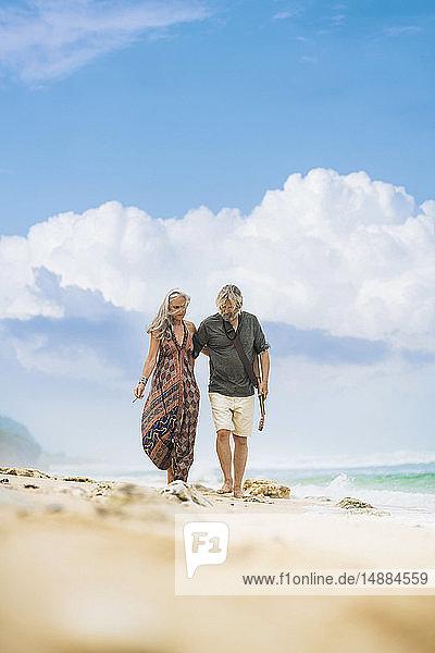 Älteres Hippie-Paar mit Gitarre Arm in Arm am Strand spazieren