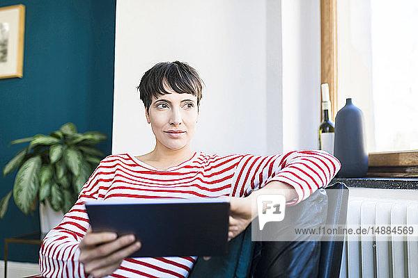 Kurzhaarige Frau entspannt sich im Sessel mit Tablett in der Hand