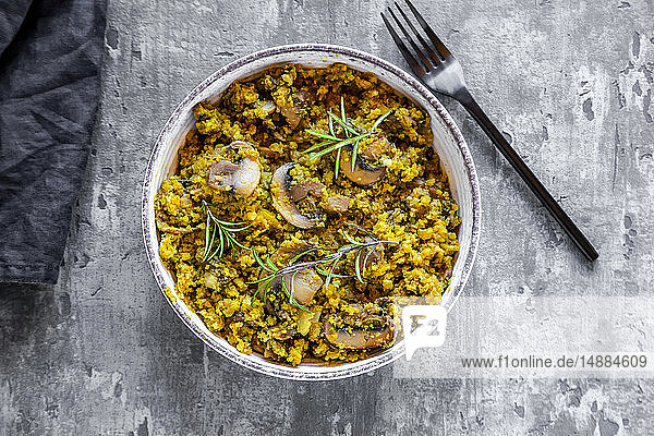 Bowl of yellow and green cauliflowers with fried champignons and rosemary