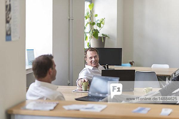 Zwei entspannte Geschäftsleute mit Laptops unterhalten sich im Büro