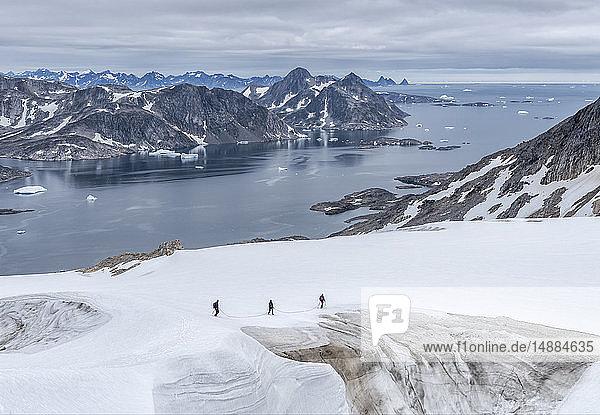 Grönland  Sermersooq  Kulusuk  Schweizer Alpen  drei Personen zu Fuss im Schnee