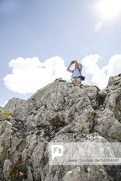 Österreich  Tirol  Frau auf einer Wanderung in den Bergen beim Fotografieren mit dem Handy