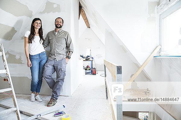 Porträt eines selbstbewussten Paares  das auf dem zu renovierenden Dachboden steht