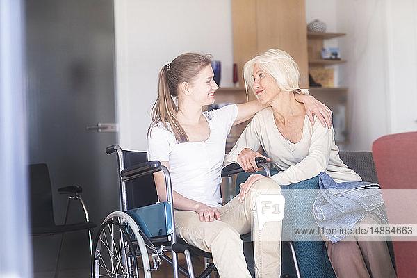 Tochter sitzt im Rollstuhl und umarmt ihre Mutter