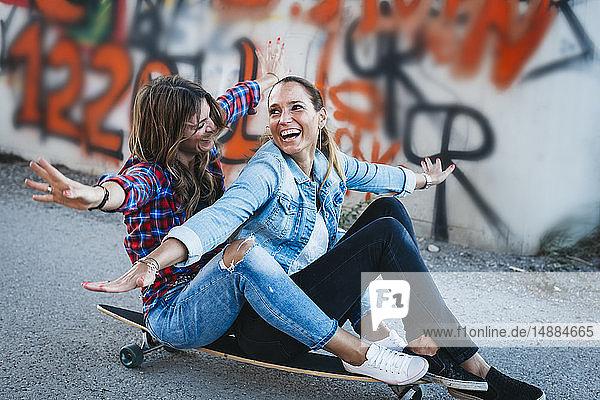 Zwei lachende Freunde sitzen mit ausgestreckten Armen auf einem Longboard