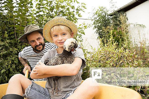Vater mit Sohn sitzt in Schubkarre mit Huhn