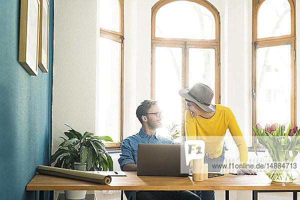 Gelegenheitsunternehmerpaar im Heimbüro  das am Laptop arbeitet und sich gegenseitig anlächelt