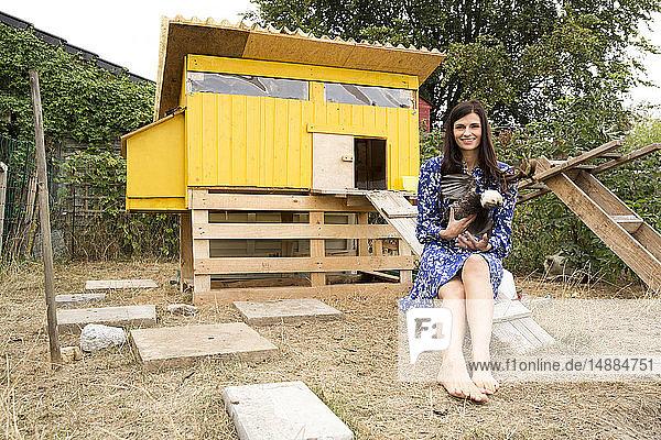 Porträt einer lächelnden Frau mit polnischem Huhn im Hühnerstall im Garten