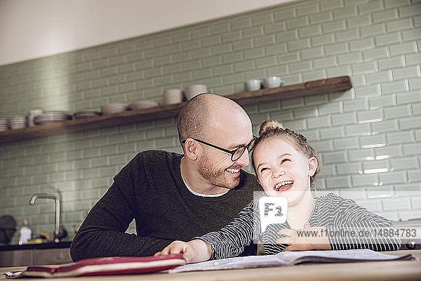 Vater und Tochter sitzen in der Küche und machen Hausaufgaben