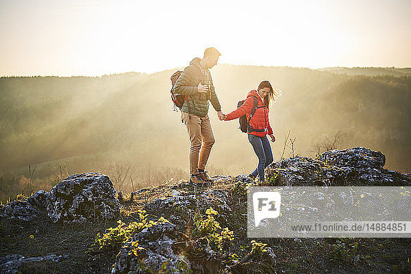 Couple on a hiking trip in the mountains walking on rocks