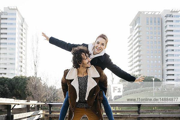 Glückliches Paar beim Huckepackritt in der Stadt
