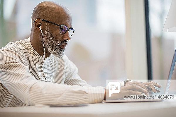 Älterer Geschäftsmann mit Kopfhörern  der am Laptop arbeitet